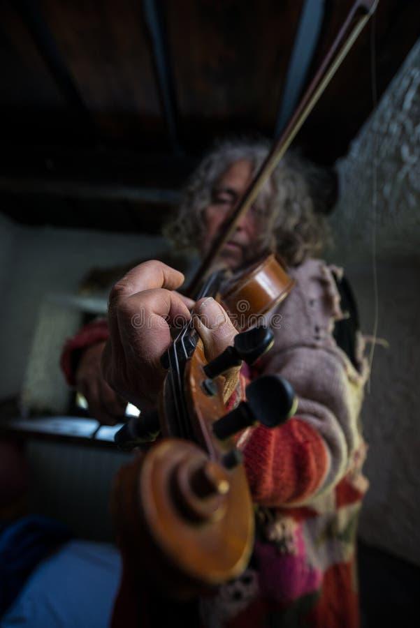 Den gamla konstnären med smutsigt spikar att tycka om hans musik, som han spelar en vio arkivfoto