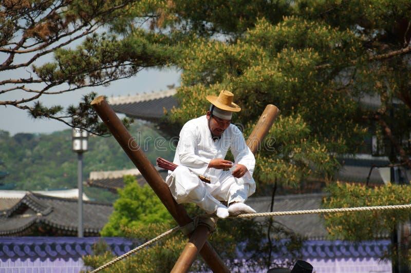 Den gamla koreanska mannen utför på spänd lina royaltyfria bilder