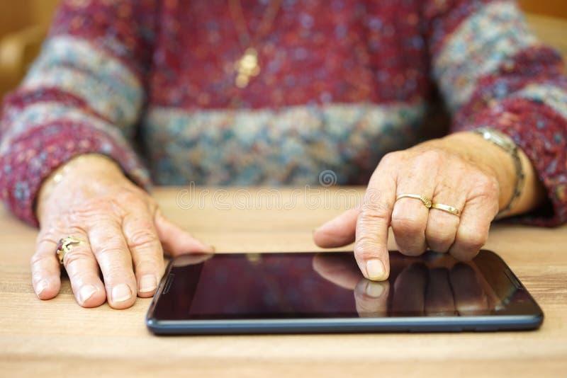 Den gamla kvinnan använder minnestavladatoren för att surfa på internet arkivfoton