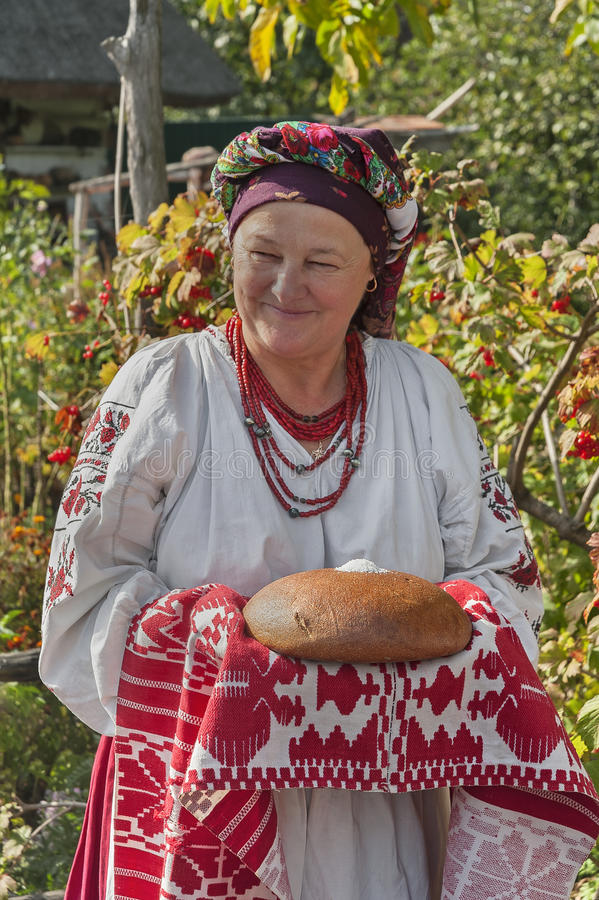 Den gamla kvinnan i ukrainsk nationell dräkt framlägger gäster med bröd i salt royaltyfri foto