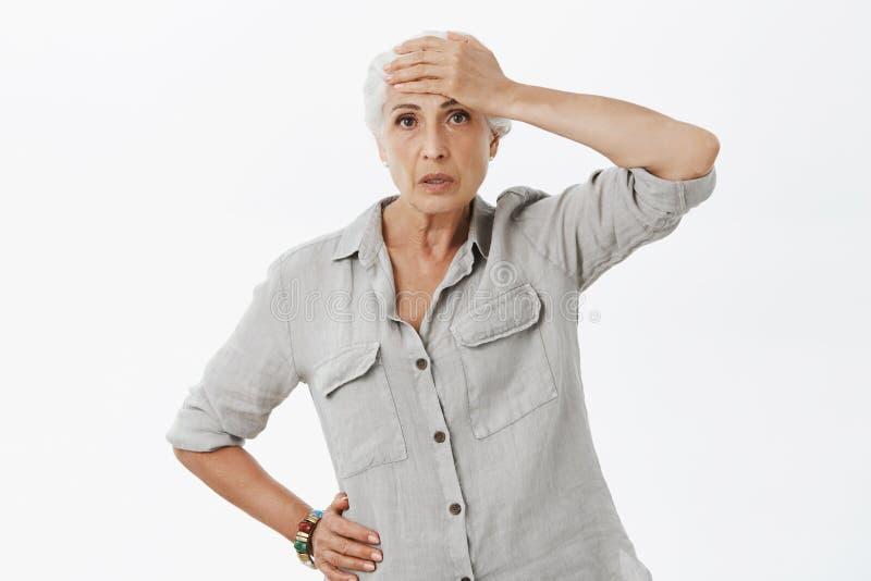 Den gamla kvinnan kan inte behandla tryck som sköter det aktiverade barnbarnet Stående av trött och tömd besvärad åldring royaltyfri foto