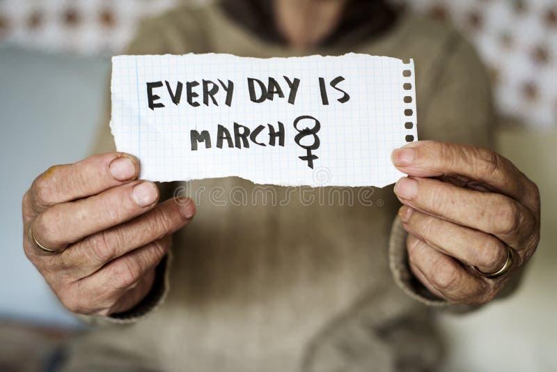 Den gamla kvinnan och smsar varje dag är marsch 8 royaltyfria foton