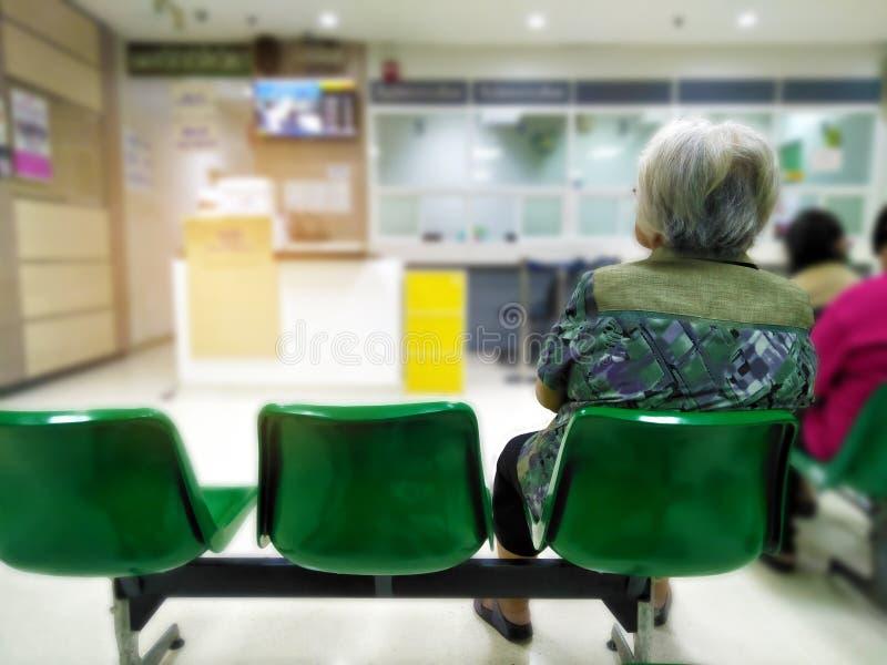 Den gamla kvinnan sitter på läkarundersökning och hälsovård för grön stol väntande till sjukhuset royaltyfria foton