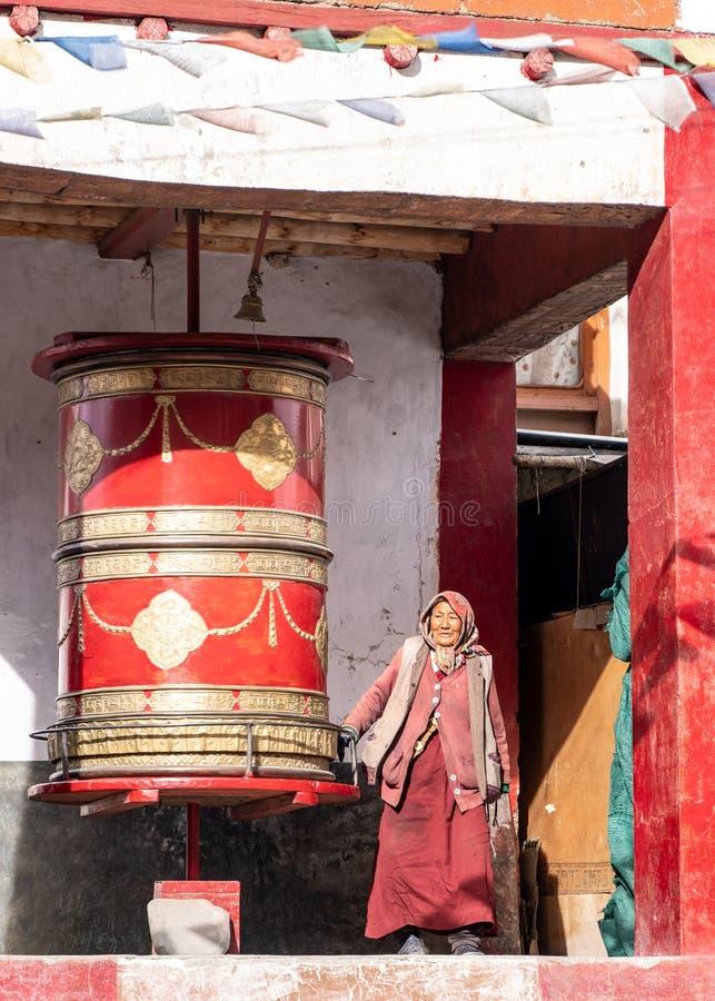 Den gamla kvinnan som går runt om den runda buddistiska valsen arkivfoton