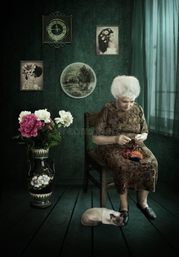 Den gamla kvinnan sticker en krok vid fönstret arkivfoto