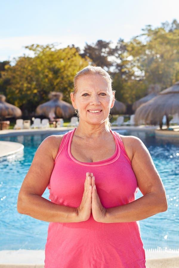 Den gamla kvinnan viker händer i yogameditation arkivfoto