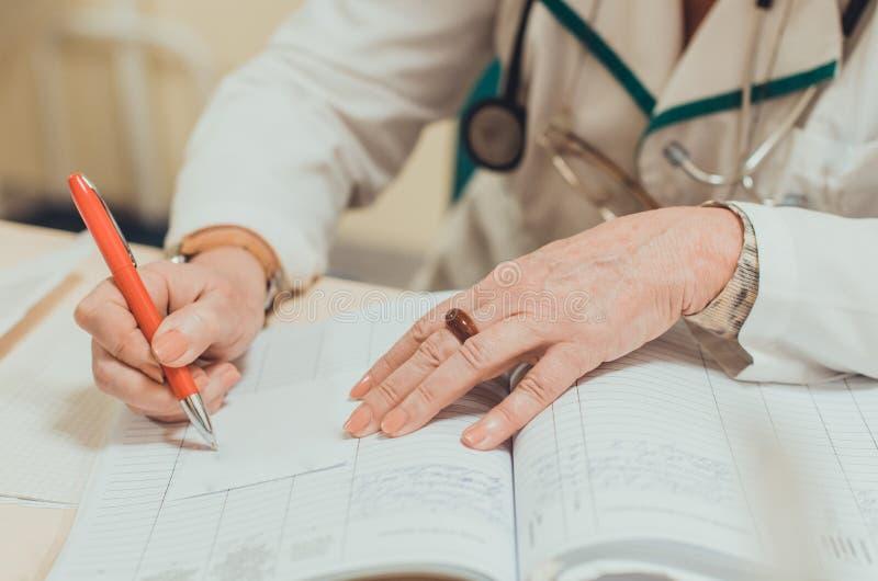 Den gamla kvinnlign erfor doktorn som skriver ett medicinskt recept royaltyfri fotografi