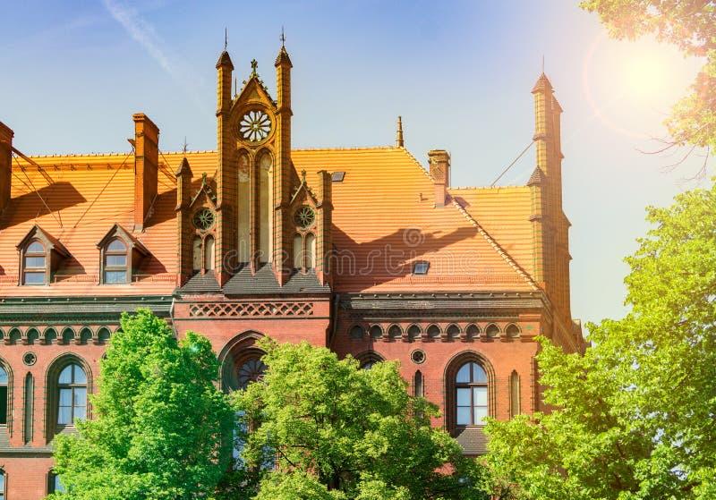 Den gamla kyrkan är upplyst vid solen, det härliga landskapet av tegelstenbyggnaden bak träden royaltyfri bild