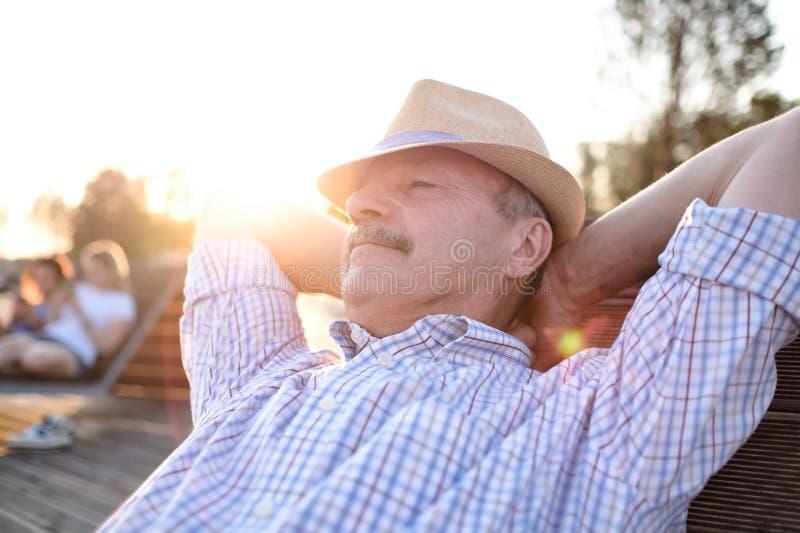 Den gamla latinamerikanska mannen sitter på bänk och att le som tycker om solig dag för sommar fotografering för bildbyråer
