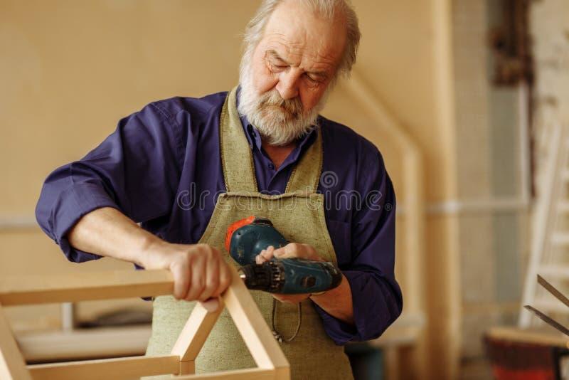 Den gamla mannen att bry sig för fåglar danandefågelförlagematare från naturligt trä royaltyfria foton