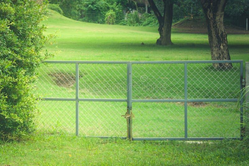 Den gamla metallporten är den inlåsta härliga trädgården royaltyfri bild