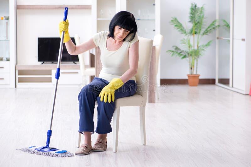 Den gamla mogna kvinnan tröttade efter hussysslor arkivfoto