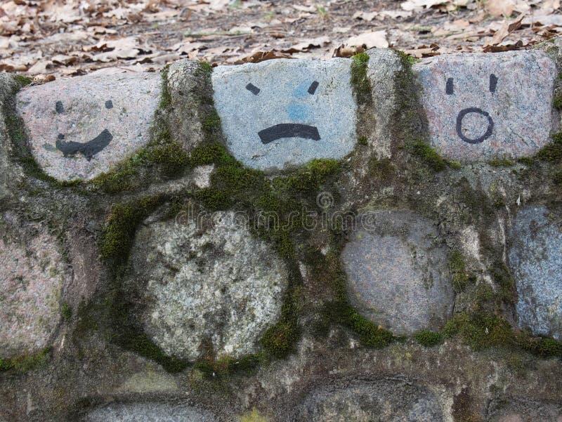 Den gamla mossiga stenväggen med den drog handen vänder mot arkivbild