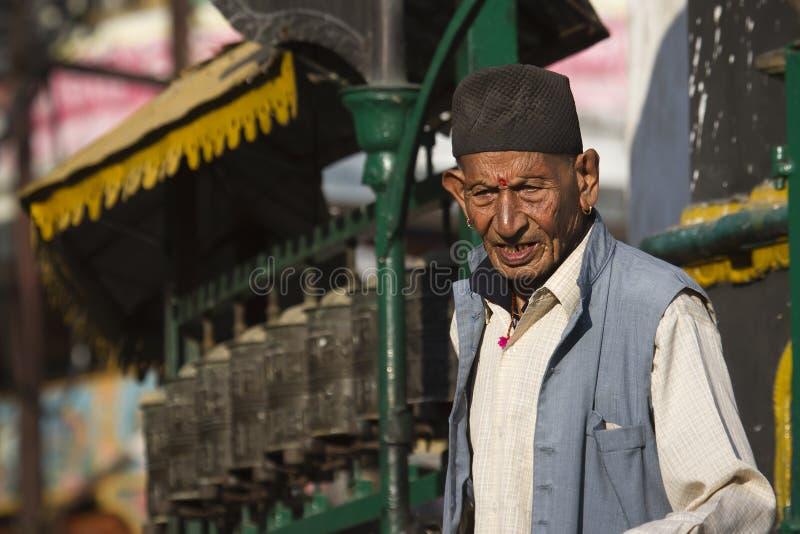 Den gamla nepalimannen framme av den buddistiska bönen rullar in Nepal, den Soyambunath templet, Katmandu royaltyfri fotografi