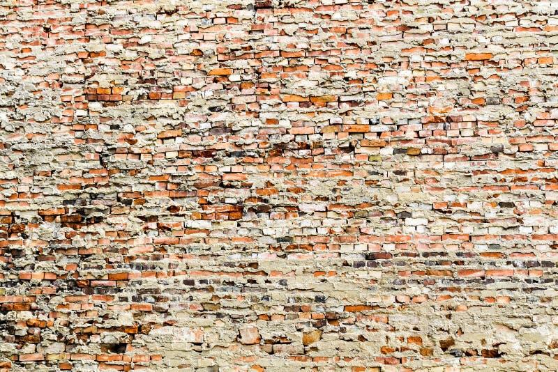 Den gamla och red ut grungy väggen för röd tegelsten som täckas delvis av överskott cement och grå färger, målar arkivfoto