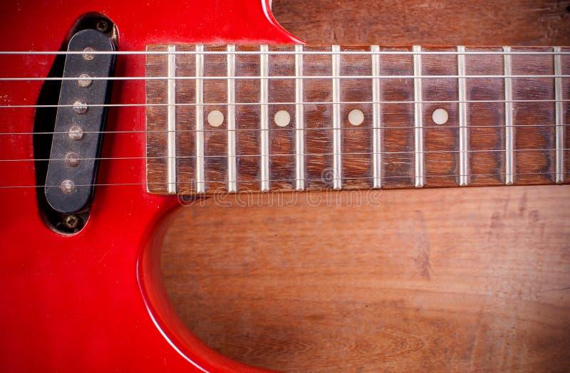 Den gamla röda elektriska gitarren som förläggas på ett trägolv arkivbilder
