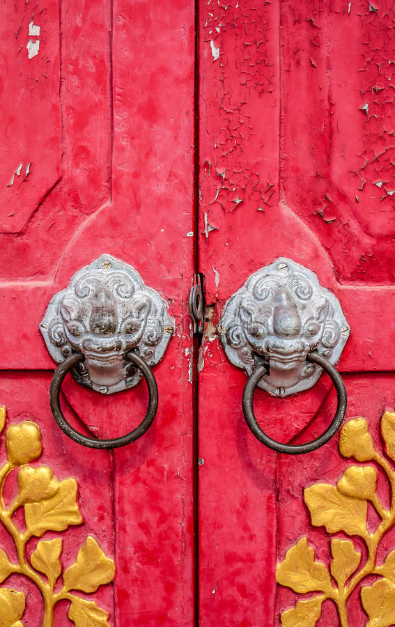 Den gamla röda kinesiska tempeldörren med kräver bladet arkivfoto
