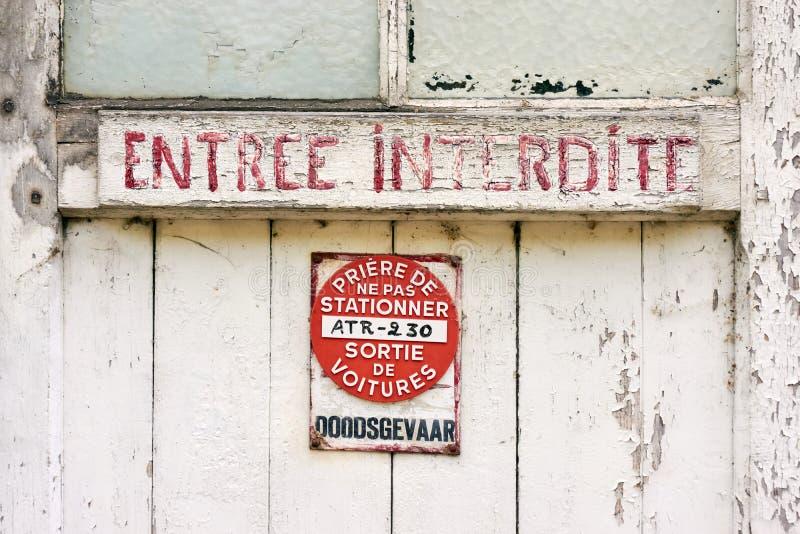 Den gamla red ut dörren med röd målad text och ingen parkering undertecknar royaltyfri fotografi