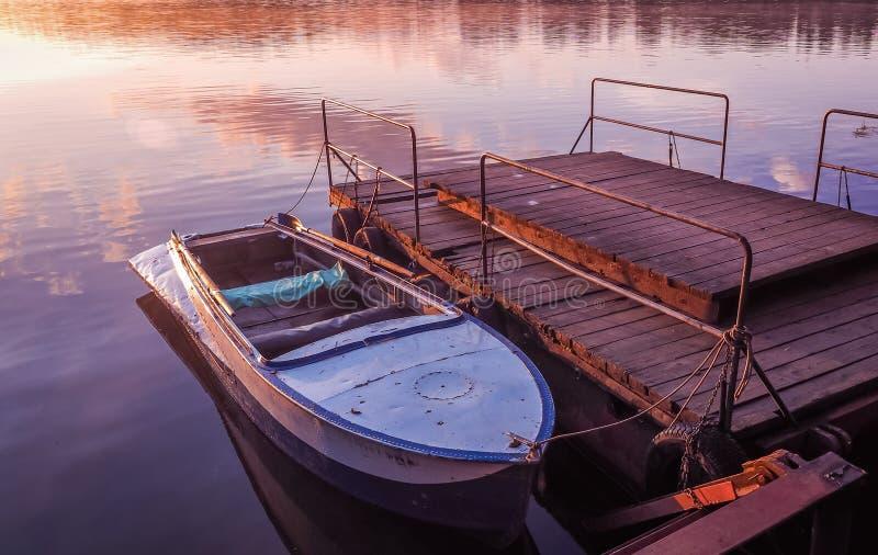 Den gamla roddbåten förtöjde för solnedgångsjön för pir den fantastiska floden arkivbild
