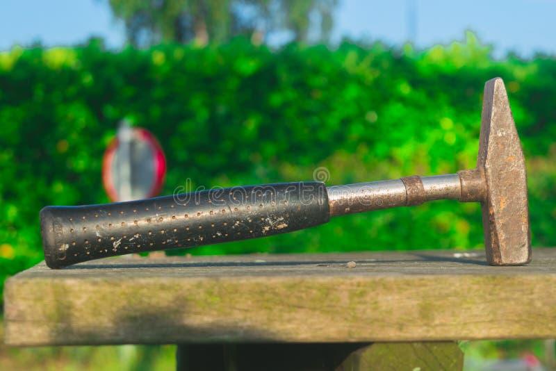 Den gamla rostiga hammaren lägger på trä arkivfoto