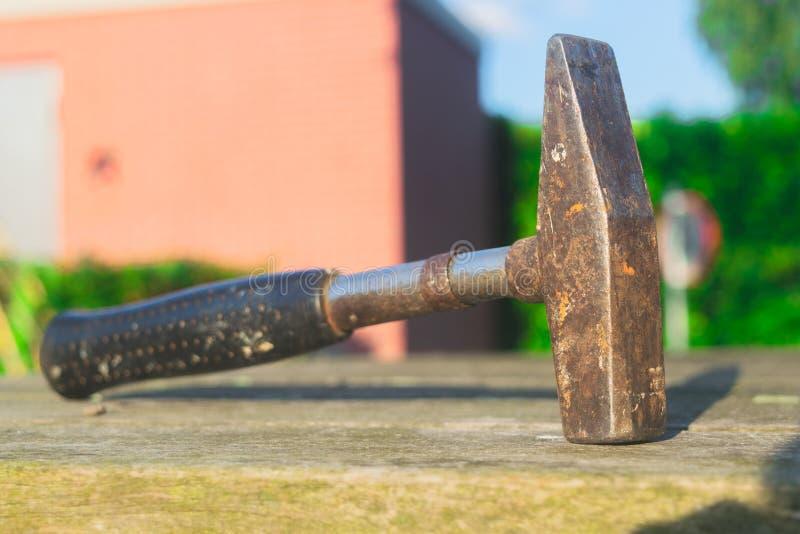 Den gamla rostiga hammaren lägger på trä royaltyfri bild