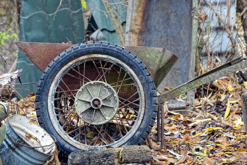 Den gamla rostiga skottkärran med ett stort rullar in gården fotografering för bildbyråer