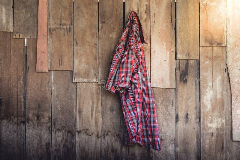 Den gamla rynkiga plädskjortan som hänger på träbakgrund royaltyfria bilder