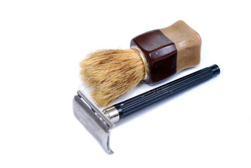 Den gamla säkerhetsrakkniven och den lilla borsten på en vit bakgrund Produkter för personlig omsorg för att raka royaltyfri bild