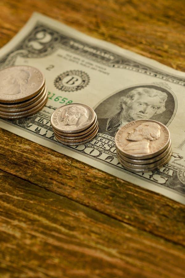 Den gamla sedeln av två US dollar och skrapade cent USA ligger på a arkivbild