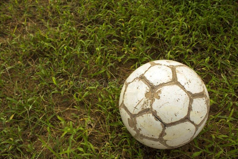 Den gamla sjaskiga vita fotbollbollen ligger på en suddig bakgrund av grönt gräs royaltyfri foto