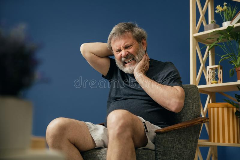 Den gamla skäggiga mannen som lider från, smärtar royaltyfri foto