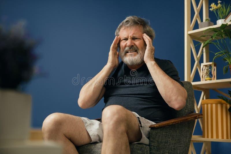 Den gamla skäggiga mannen som lider från, smärtar arkivfoton