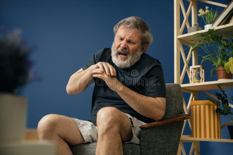 Den gamla skäggiga mannen som lider från, smärtar arkivbilder
