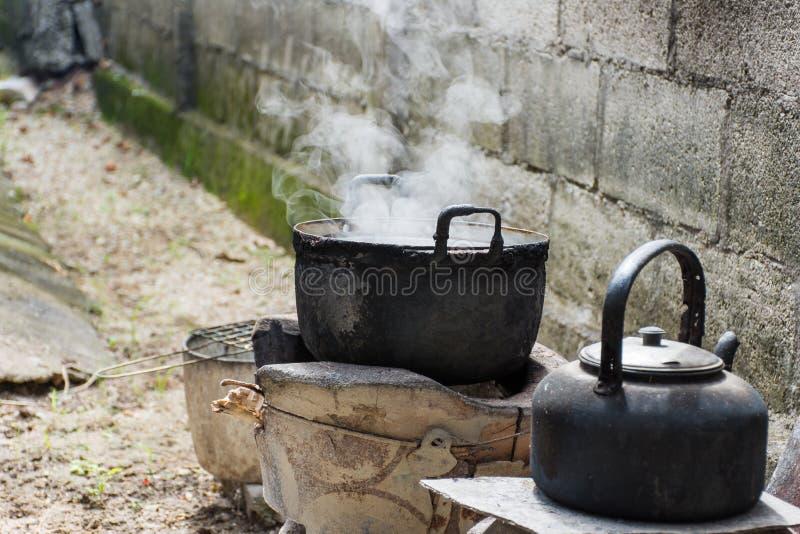 Den gamla smutsiga matlagningkrukan och bunken kokade vatten med ånga arkivbild