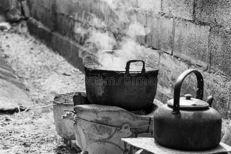 Den gamla smutsiga matlagningkrukan och bunken kokade vatten med ånga royaltyfri foto