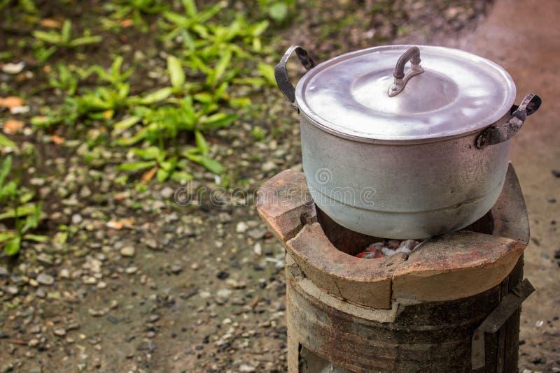 Den gamla smutsiga matlagningkrukan och bunken kokade vatten med ånga royaltyfri fotografi