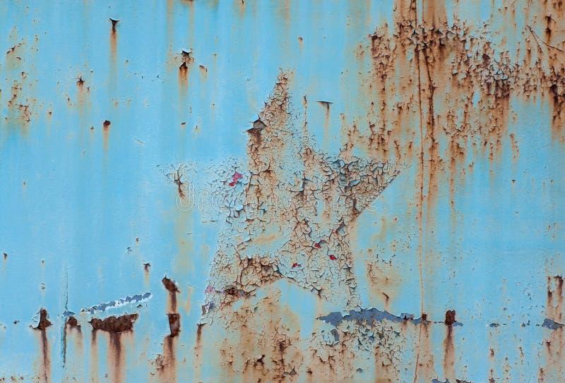 Den gamla sovjetiska stjärnan syntes under blå kulör målarfärg på den rostiga stålplattan Textur/bakgrund arkivbilder