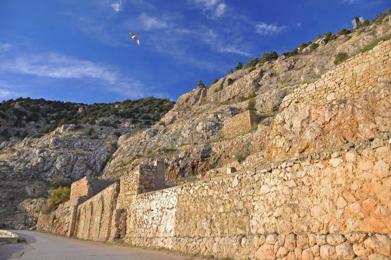 Den gamla stenen stärkte väggen står hög i bergen mot den blåa himlen royaltyfri fotografi