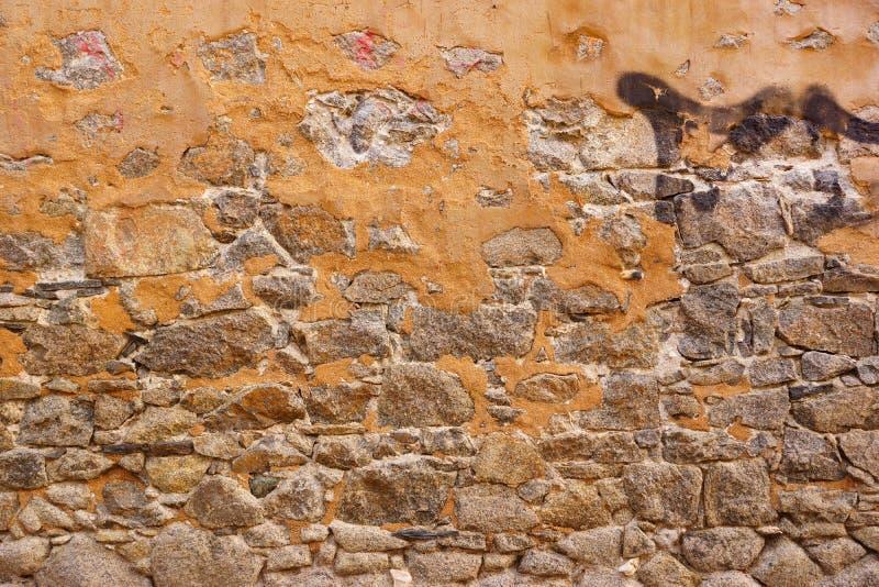 Den gamla stenväggen som göras från granit, vaggar och rev sönder murbruk arkivbilder