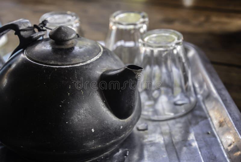 Den gamla svarta tekannan med tre klara exponeringsglaskoppar ställde in på rostfritt stålmagasinet royaltyfri foto