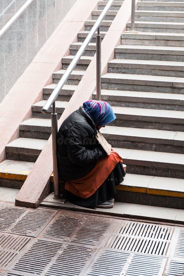 Den gamla tiggarekvinnan sitter på trappan fotografering för bildbyråer