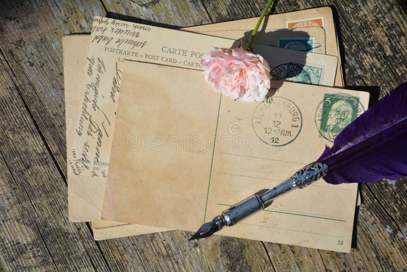 Den gamla tomma tappningvykortet med den gamla stämpeln är på gammalt trä med rosa färgrosen och niboldträ med det rosa färgrosen arkivfoto