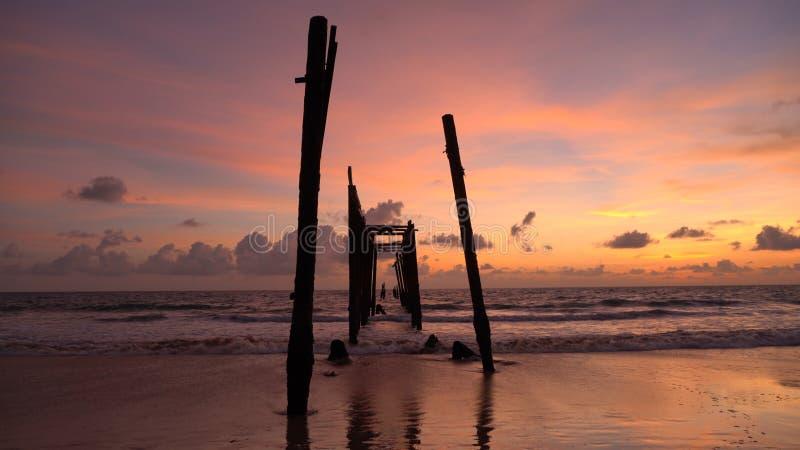 Den gamla träbro- och havsvågen på stranden på solnedgånghimmelbakgrund på Khao Pilai, Phangnga, Thailand ?pplet clouds treen f?r arkivfoto