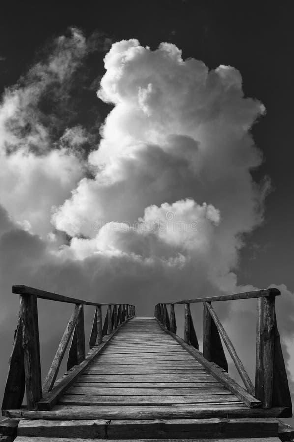 Den gamla träbron leder till okända mot himmel och fördunklar arkivfoton