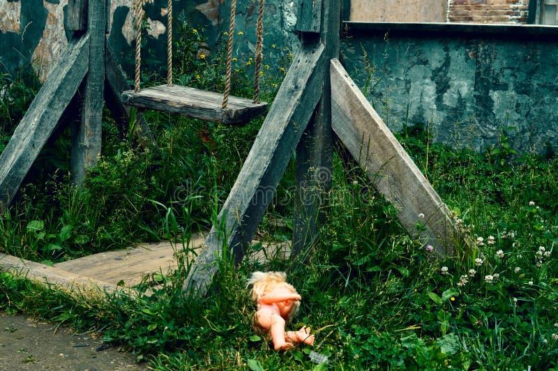 Den gamla träbrutna gungan Den glömda plast- dockan i ett gräs royaltyfri bild