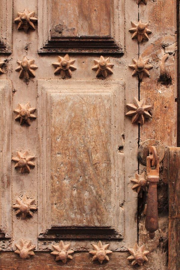 Den gamla trädörren med smidesjärn specificerar den formade trappan royaltyfria foton