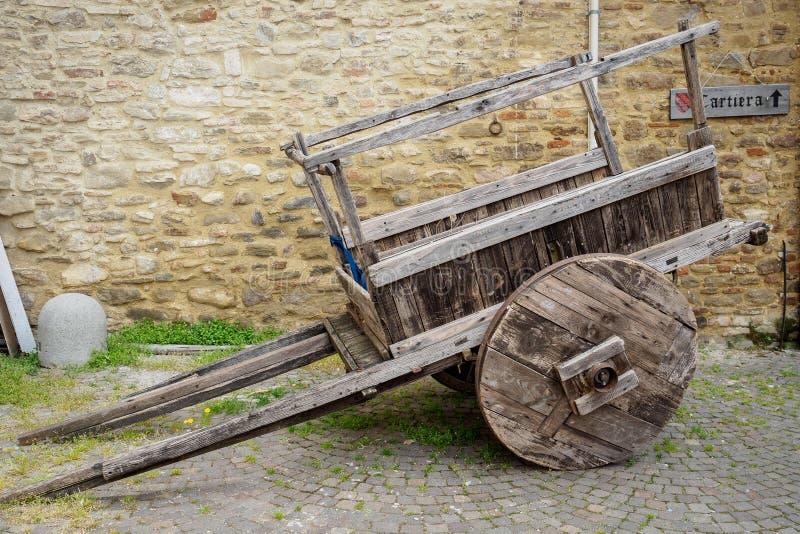 Den gamla trävagnen med en stenmurverkvägg på bakgrunden med ett cartierateckenpapper maler i italienskt språk royaltyfri fotografi