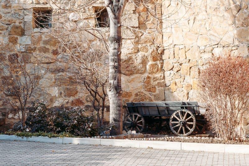 Den gamla trävagnen mot bakgrund av konstigt stenar väggen av fästningen royaltyfri bild