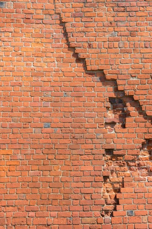 Den gamla väggen för röd tegelsten har en spricka fotografering för bildbyråer