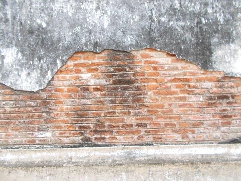 Den gamla väggen för röd tegelsten och gammal sprucken konkret tappningbakgrund texturerar, den smutsiga svampen royaltyfri fotografi